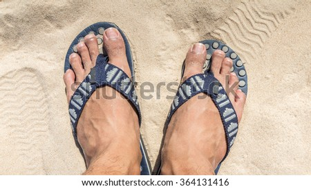 Man feet wearing blue flip flops on a beach - stock photo