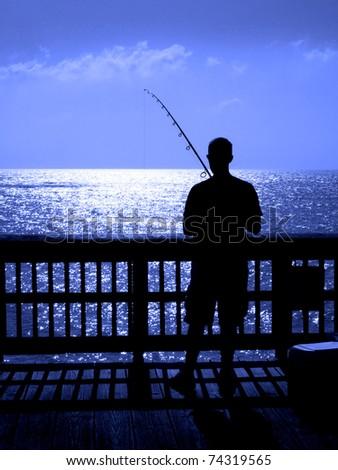 Man ffishing in ocean from a wooden pier - stock photo