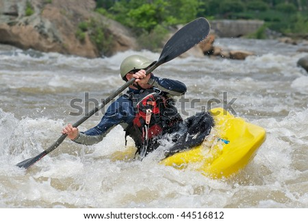 Man fighting the rapids of a river in a kayak. - stock photo