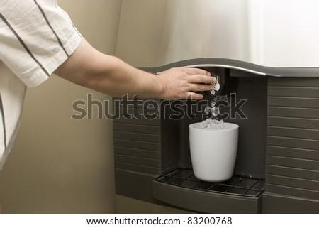 Man filling bucket from Ice machine - stock photo