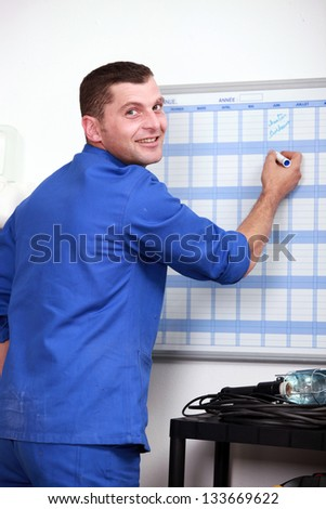 Man filling in wall schedule - stock photo