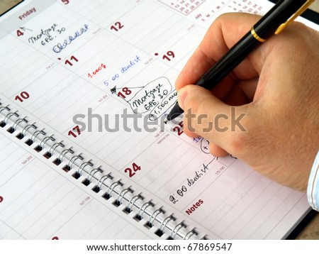 Man filling out  monthly planner on the table