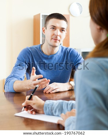 Man  filling questionnaire for employee with paper at table in office - stock photo