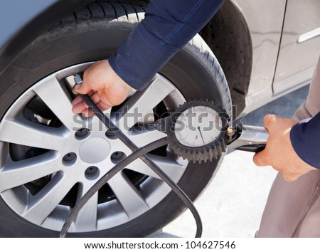 Man fills tire in car - stock photo