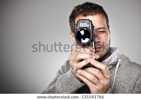 Man filming with a video camera. / Portrait of a normal man with video camera over grey background. - stock photo