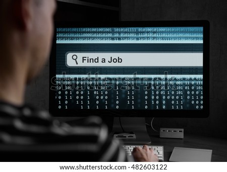 man finding for a job online on a computer. Rear view.