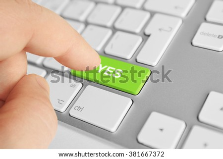 "Man finger pushing ""Yes"" button on pc keyboard - stock photo"