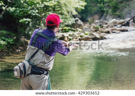 Man fisherman catching trout in the river fishing rod. Fly fishing in a forest creek in Europe. Professional sport angler catches a fish. - stock photo