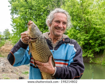 Man fisherman caught a large freshwater carp. Fisherman with trophy on the banks of the river - stock photo