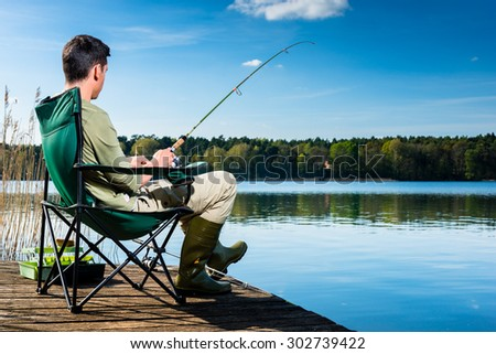 Man fishing at lake sitting on jetty close to the water - stock photo