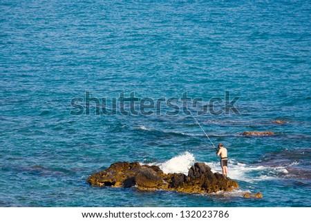 Man  fishing at the beach - stock photo