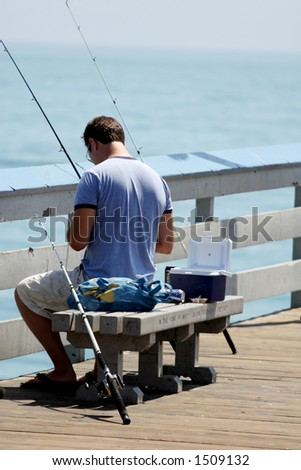 Man fishing from pier. - stock photo