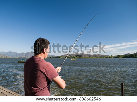 Man fishing in the summer at Rapel Lake, Chile