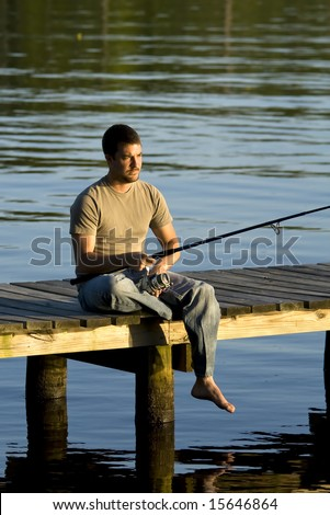 Man fishing on a dock in the bay as the sun is setting. - stock photo