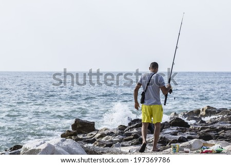 Man fishing on the coast - stock photo