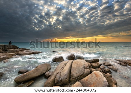 Man fishing on The stone in The sea  - stock photo