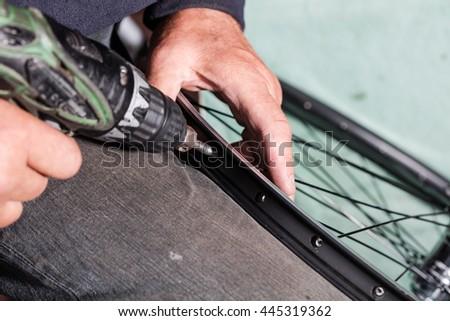 Man fixing bicycle rim, wheels manufacturing. - stock photo