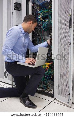 Man fixing wires while doing maintenance with laptop in data center - stock photo