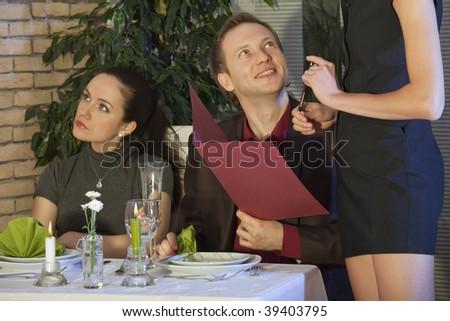 man flirting with waitress, his girlfriend sitting unhappy - stock photo