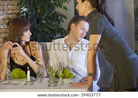 man flirting with waitress in a restaurant - stock photo