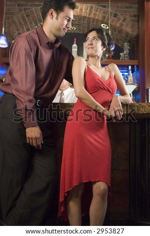 Man flirting with woman at a bar - stock photo
