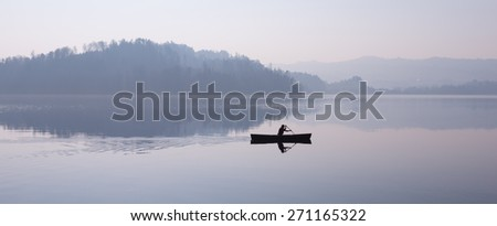 Man floating in a boat. Fog over lake Zug, mountains reflected in the water. Switzerland - stock photo