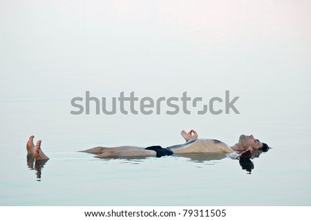 Man floating in a glassy water of dead sea with outstretched arms and chin mudra