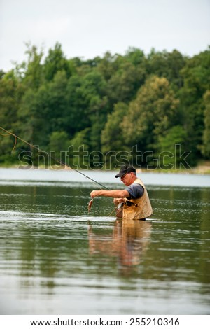 Man fly fishing on calm river - stock photo