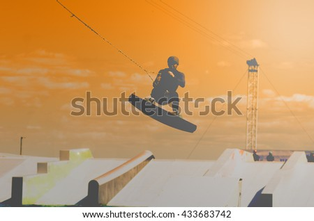 Man fly with wakeboard. Boy making extreme trick. Ogange concept.