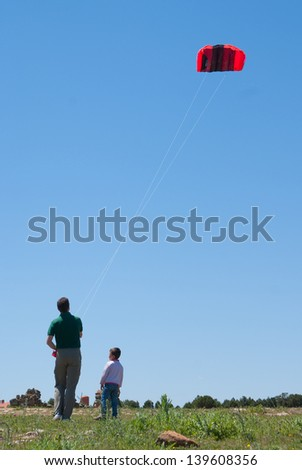 Man flying a kite in a sunny day with his son - stock photo