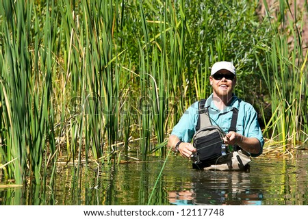 Man flying fishing in a lake against green reeds with a big smile on his face - stock photo