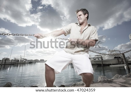 Man forcefully tugging on a chain - stock photo