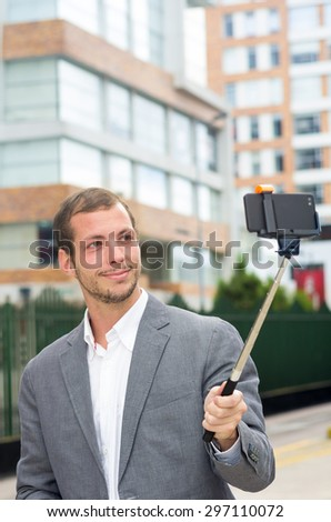 Man formal clothing posing with selfie stick in urban environment. - stock photo