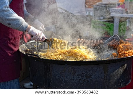 Man fries noodles on big frying pan, on street