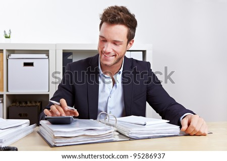 Man from internal revenue doing tax audit with calculator in office