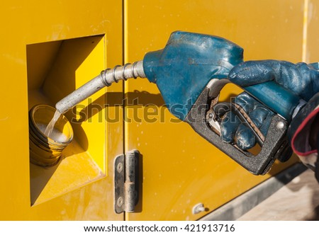 Man fueling compressor with diesel. Fuelling gasoline in car.