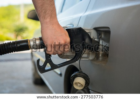 Man fueling up a car - stock photo