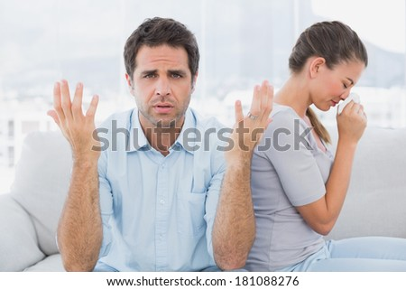 Man gesturing at camera with his crying partner on the couch at home in the living room - stock photo