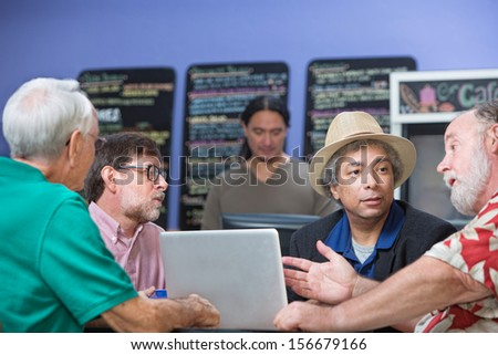 Man gesturing while talking with friends in cafe - stock photo
