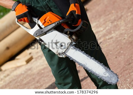Man gets on the hip chainsaw - stock photo