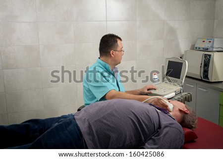 man gets ultrasound of the thyroid from doctor - stock photo