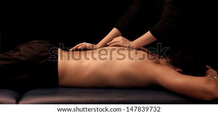 Man getting a back massage at spa, by a masseuse