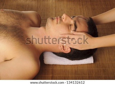 Man getting a face massage, at spa