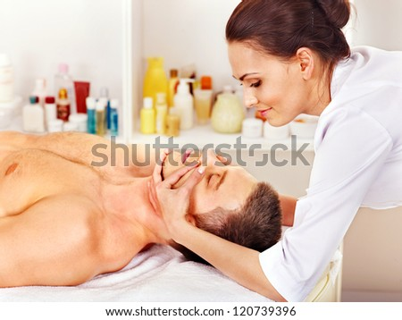 Man getting facial  massage in beauty spa. - stock photo
