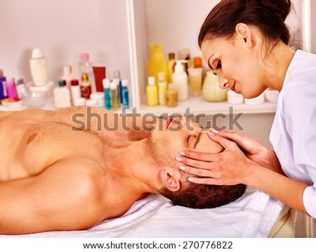 Man getting facial  massage in beauty spa. Hand on head. - stock photo
