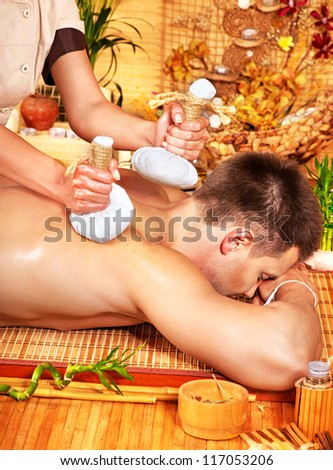 Man getting herbal ball massage treatments  in spa.