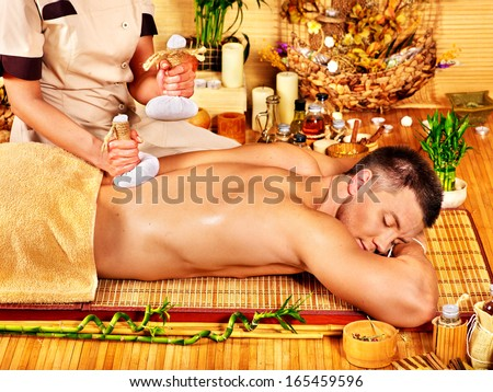 Man getting herbal ball massage treatments  in spa..
