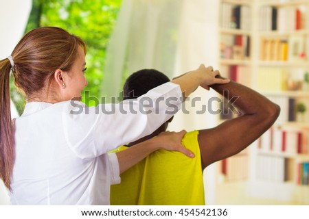 Man getting physical arm treatment from physio therapist, her hands working on his shoulder and elbow, medical concept