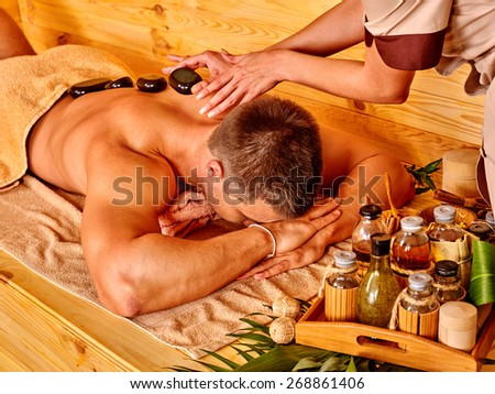 Man getting stone therapy massage in bamboo spa. Face is not visible. - stock photo