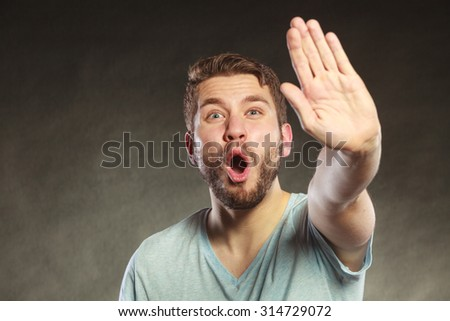Man give stop hand sign gesture. Facial expression open mouth black background.